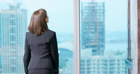 ponderar : businesswoman look outside through the windor and ponder