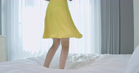 buzağı : Fashion young lady feel carefree and jump on the bed in a hotel room while traveling Stok Video