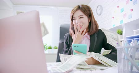 технология : Make money on the Internet concept - slow motion of asian business woman excited with banknote from computer and smartphone Стоковые видеозаписи