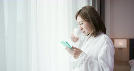 мотель : beauty asian woman use smart phone with coffee and enjoy a wonderful morning in the hotel