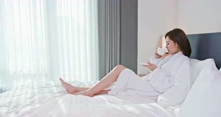 vakáció : beauty asian woman drink coffee and enjoy a wonderful morning in the hotel Stock mozgókép