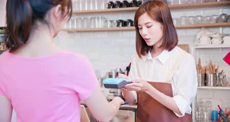 crediti : mobile payment concept - In the Cafe Woman Makes Takeaway Coffee For a Customer Who Pays by Contactless Phone to Credit Card System Filmati Stock
