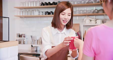 бумажник : mobile payment concept - In the Cafe Woman Makes Coffee For a Customer Who Pays by Contactless Phone to Credit Card System
