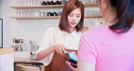 nfc : mobile payment concept - In the Cafe Woman Makes Takeaway Coffee For a Customer Who Pays by Contactless Phone to Credit Card System Stock Footage