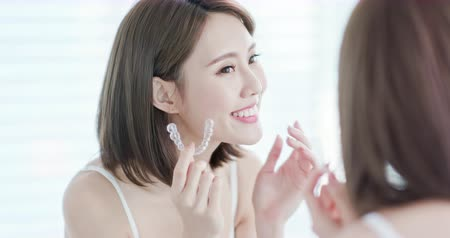 teeth with braces : Asian woman look at the mirror with invisible braces in the morning Stock Footage