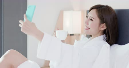 estilo de vida : beauty asian woman take selfie by smart phone and enjoy a wonderful morning in the hotel