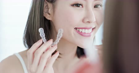 invisible : beauty woman look at the mirror and take off the invisible braces