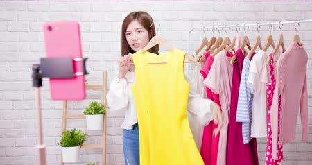 película de filme : beauty female fashion vlogger presenting yellow dress to cellphone and smiling showing clothes selling online live streaming Stock Footage