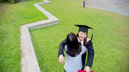 хозяин : Girl gratuate give friend a hug happily in the campus