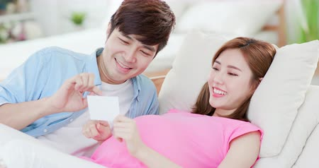 ultrasound scan : Happy pregnant woman with husband looking at ultrasound photo at home Stock Footage