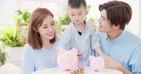 earnings : family saving money and putting coins into piggy bank Stock Footage