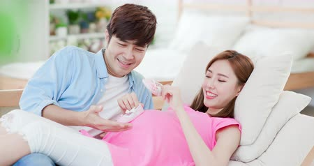 stomach : happy pregnant woman with husband holding the baby shoes at home Stock Footage
