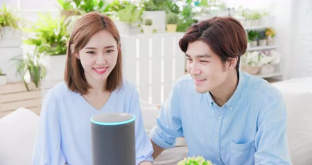 perguntando : Smart AI speaker concept - Young couple talk to voice assistant at home and feel happy