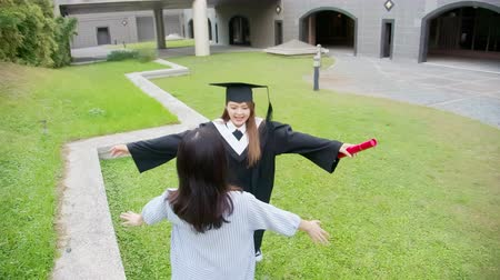 master's degree : Girl gratuate give friend a hug happily in the campus