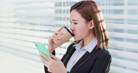 asistan : business woman use smart phone and drink coffee happily in office