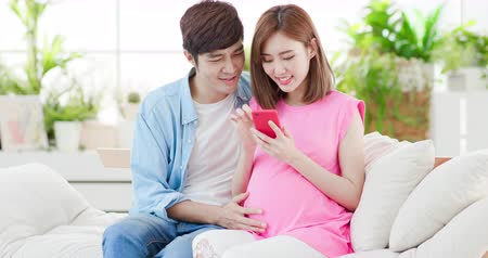narození : happy pregnant couple use smart phone at home