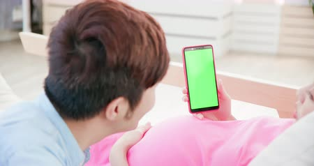 妊娠した : pregnant woman and her husband looking at phone with green screen
