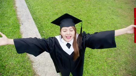 master's degree : Girl gratuate lift arm happily with diploma holding in hand