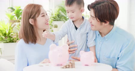 save the animals : family saving money and putting coins into piggy bank Stock Footage