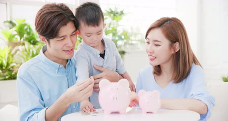 ailelerin : family saving money and putting coins into piggy bank Stok Video