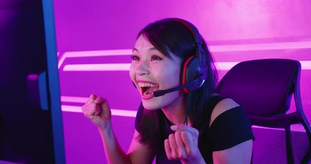 raising fist : Young Asian Pretty Pro Gamer win in Online Video Game