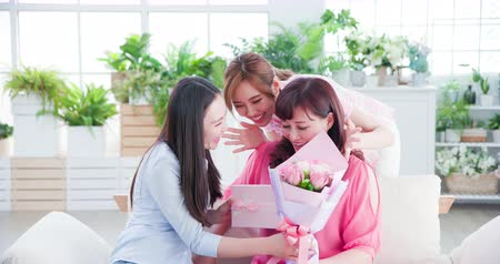 положительный : two daughters give mom a surprise and celebrate happy mother day at home