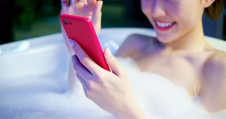 película de filme : slow motion of woman use smart phone happily while bathing at night Stock Footage