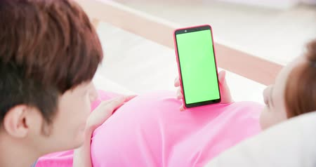 anyai : pregnant woman and her husband looking at phone with green screen