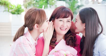 emekli olmak : two daughters give flowers to her mom and chat happily at home