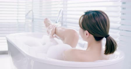 coxa : slow motion of asian woman taking a bubble bath and touch her leg