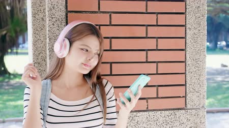mobile music : asian beauty student listen to the music with the smart phone Stock Footage