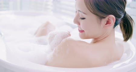 a smile : slow motion of asian woman taking a bubble bath in the bathroom