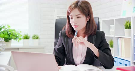 olhando para baixo : Young asia woman work in office and write down something
