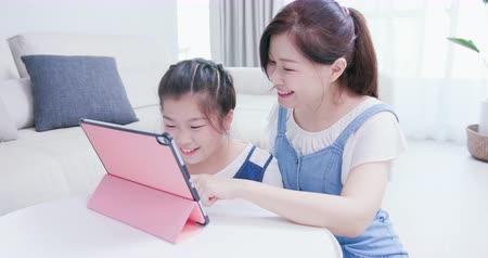 e learning : Mom and daughter use tablet happily in living room
