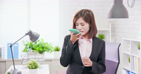 perguntando : Asian businesswoman use audio assistant by smart phone in the office