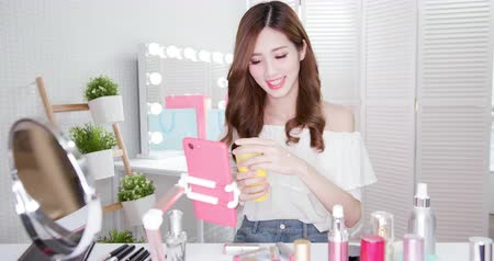 sunblock : beauty female fashion vlogger woman show sunscreen products in live stream by smartphone Stock Footage