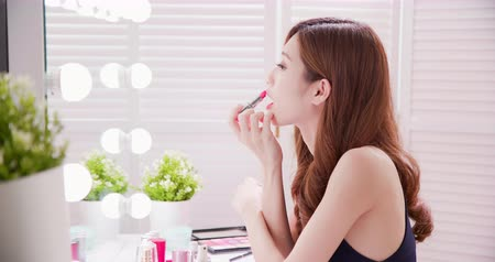 cuidados com a pele : Woman look in in the mirror and use the lipstick Stock Footage