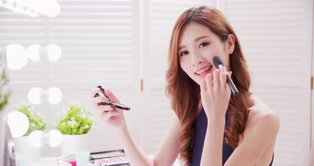 puder : Smile asian woman with makeup brushes near face and smile to you at home