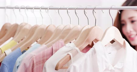 denemek : young woman choosing clothes on a rack in a showroom Stok Video