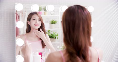 krk : beauty skin care woman smile and apply cream on neck in the mirror