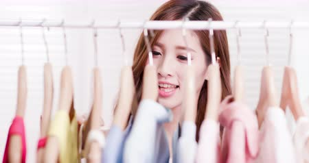 vállfa : young woman choosing clothes on a rack at home Stock mozgókép