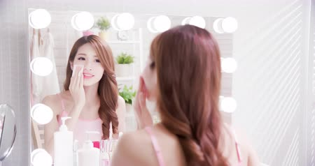 čelo : Close up of smile asian beauty woman moisturizing by cleansing cotton and look mirror