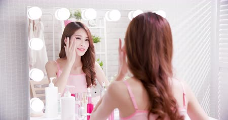 sunblock : beauty skin care woman smile and apply BB cream on face in the mirror Stock Footage