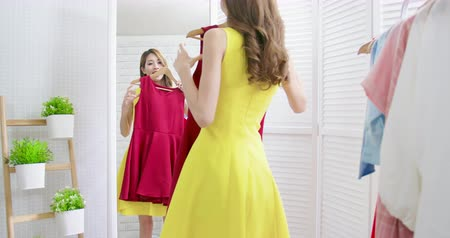 denemek : slow motion of asian girl trying the dress and looking herself in mirror cheerful