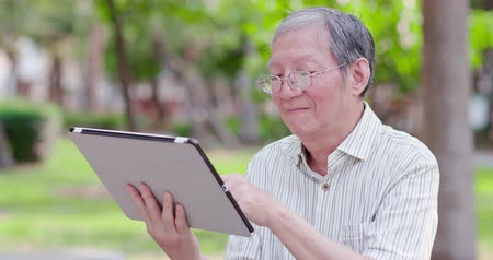 aposentar : Older man use tablet in the park Stock Footage