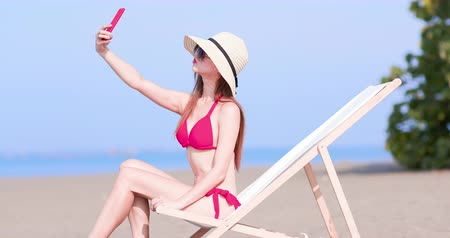 laying : bikini woman take selfie on the beach