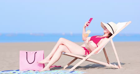cadeira : bikini woman take selfie with juice on the beach Stock Footage
