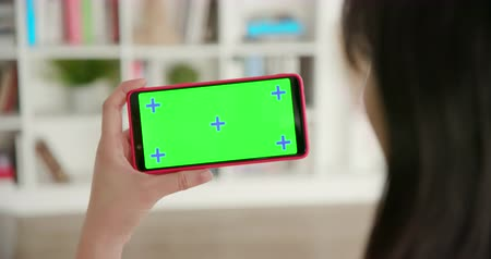 otthonok : woman use smart phone with green screen at home Stock mozgókép
