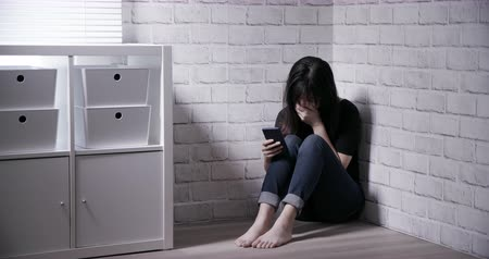 чувствовать : Asian girl feel depressed due to cyberbullying in the corner Стоковые видеозаписи