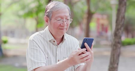 starszy pan : Older man use cellphone in the park
